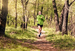 A senior man worn in black and green is running in the forest  during a warm spring day