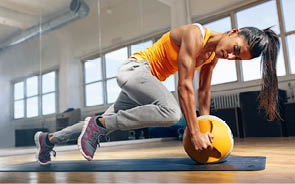 Fit female doing intense core workout in gym  Young muscular woman doing core exercise on fitness mat in health club