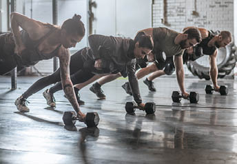 Group of men and women doing workouts together at gym