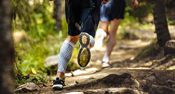 male marathon runner running woods, on feet compression socks  a dynamic and explosive running  closeup of trainers