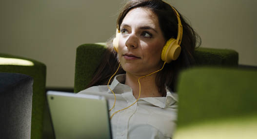 Woman with headphones looking away while using digital tablet in office    Modellfreigabe vorhanden   Mindestpreis 20 Euro